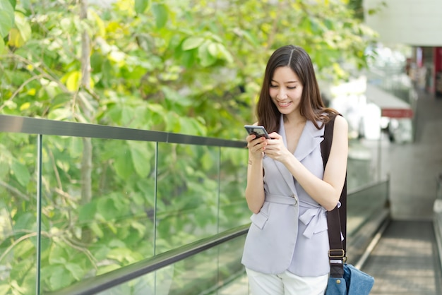 Asian office girl typing text on mobile phone standing on elevator in shopping mall.