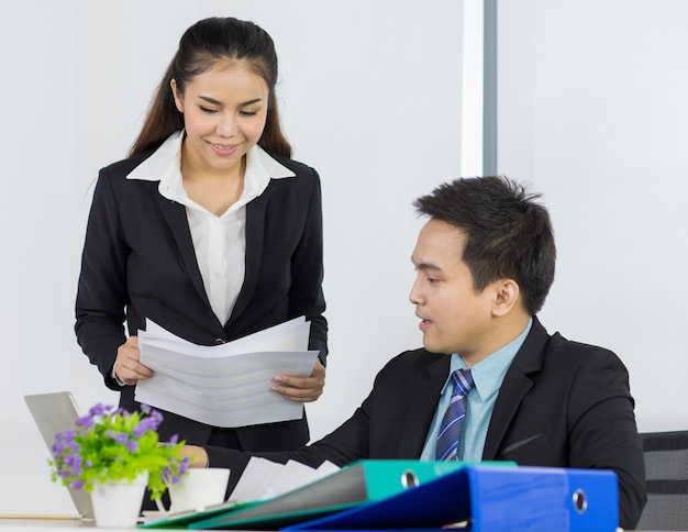 Asian office people are secretary smiling and holding document paper for presentation to boss manager while sitting and looking paper document on her hand in office place.