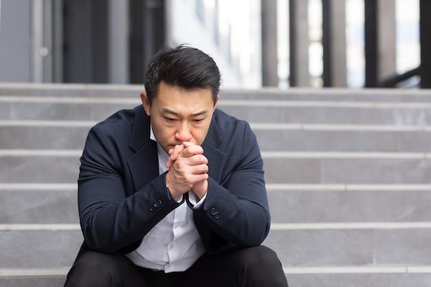仕事の結果に不満を持って、オフィスの階段に座って仕事をした後、アジアのサラリーマンマネージャーが疲れた