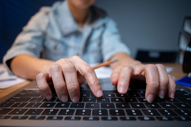 Азиатский офицер печатая компьютер для очистки своего проекта в комнате офиса. женщина малайзийских людей. работает поздно. с течением времени. тип документа для отчета с портативным компьютером.