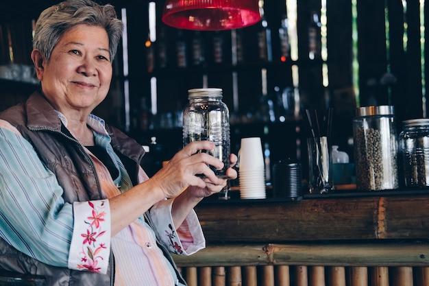 カフェショップで焙煎コーヒー豆を保持しているアジアの老婆年配の女性