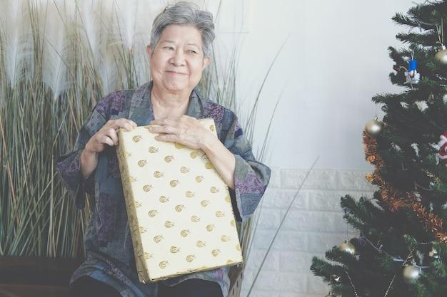 크리스마스 트리 근처 선물 선물 상자를 들고 아시아 노인 여성 노인 수석 여성