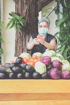 Азиатская старая пожилая женщина с фруктами и овощами в деревянной тележке с фермы