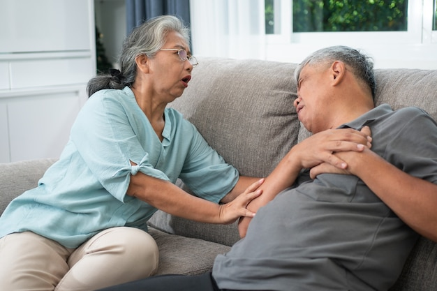 Asian old elderly man is in pain with his hands on his chest and having a heart attack in the living room