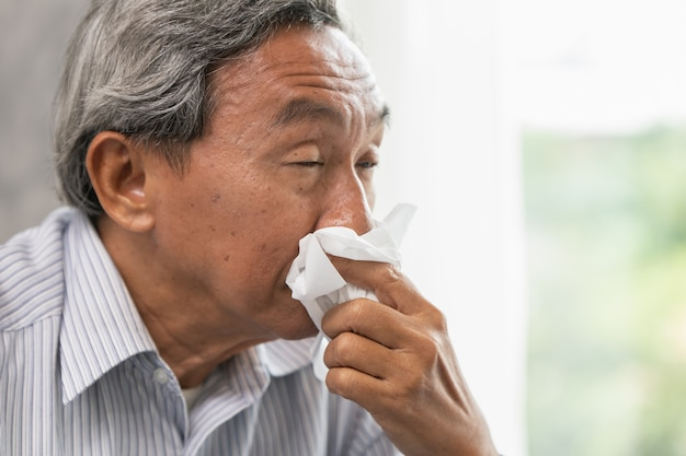 Asian old man elder get sick wipe the nose snot from flu and runny nose when season change.