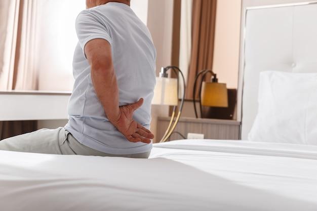 アジアの老人は寝た後に背中の痛みを抱えています