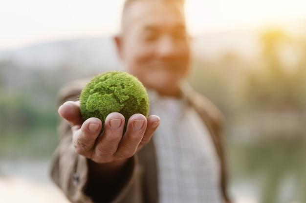 Азиатский старик показывая землю в наличии, экологию и концепцию окружающей среды устойчивую.