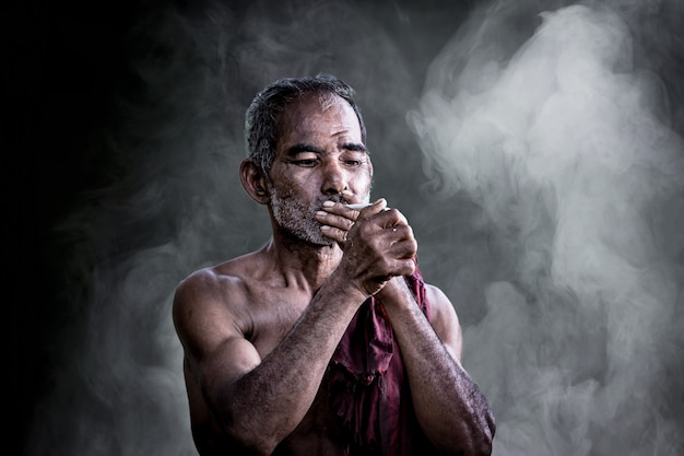 Asian old man smoking cigarette and the smoke released from the mouth against dark