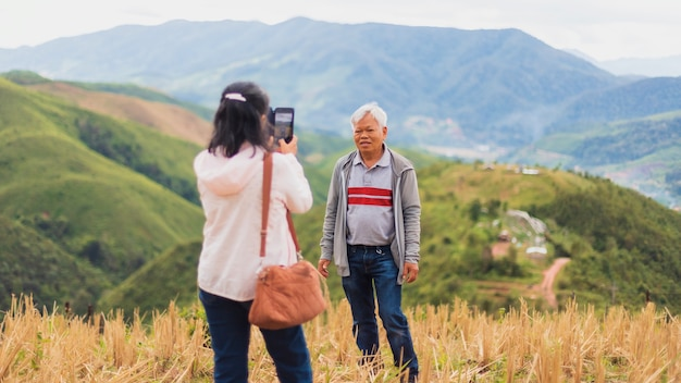 Asian old senior couples use smartphone to selfie at the top of mountain