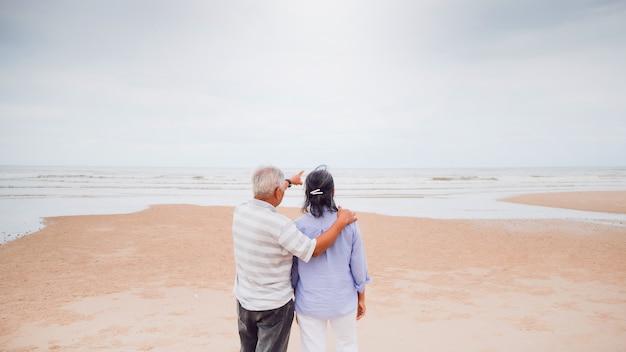 海沿いのビーチを歩くアジアの老夫婦