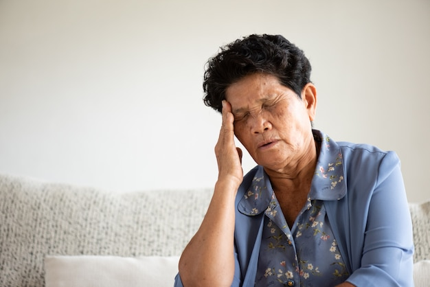 Asian old woman sitting on sofa and having a headache
