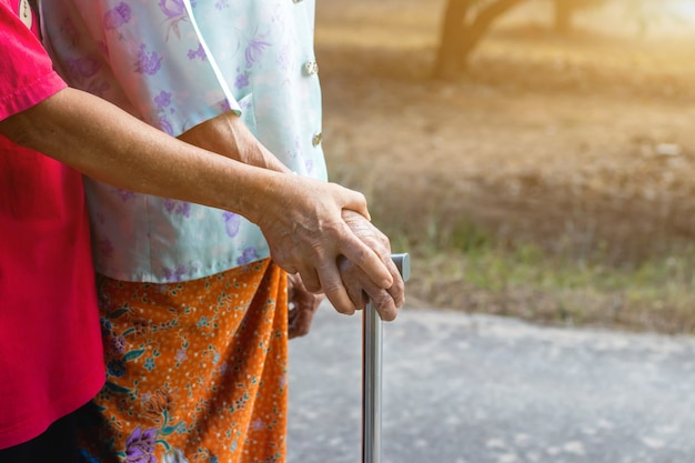 Asian old woman standing with her hand on a walker with daughter's hand