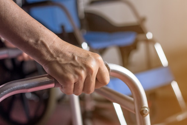 Asian old woman standing with her hands on a walker stand