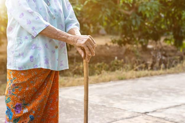 걷는 것을 돕는 대나무 지팡이 스틱을 들고 서 아시아 늙은 여자