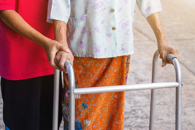 Asian old woman standing with walker with daughter's hand for helping walking