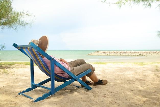 日よけ帽をかぶったアジアの老婆は、ビーチのそばのデッキチェアに横になります。定年中の高齢者の自然観光の概念。コピースペース