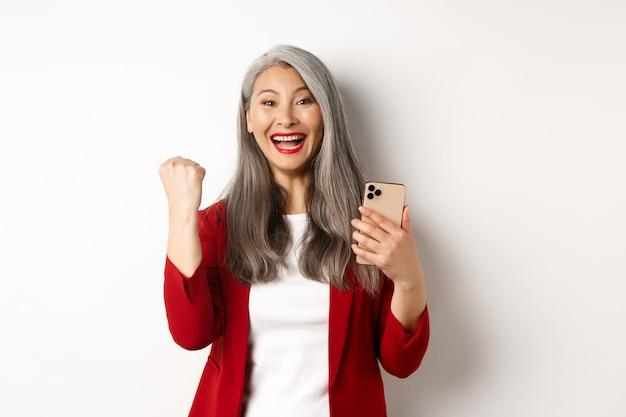 아시아 늙은 여자 온라인 승리, 스마트 폰을 들고 주먹 펌프 제스처를 만들어 승리를 축하하고 승리하고 웃고, 흰색 배경 위에 서 있습니다.