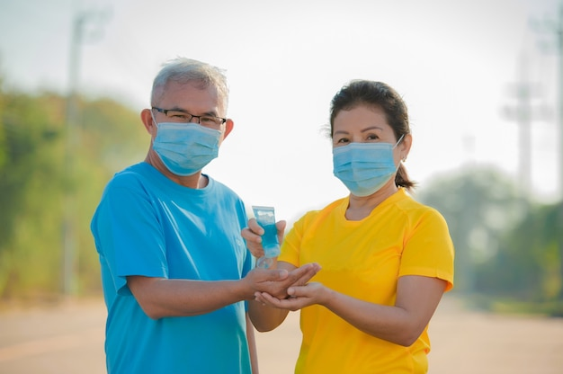 Asian older couple wear face mask use alcohol gel for cleaning hand protect coronavirus covid 19 ,senior man women old insurance