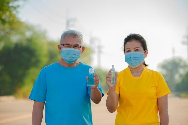 아시아 노인 커플 착용 얼굴 마스크 사용 손 청소를위한 알코올 젤 보호 코로나 바이러스 covid 19, 노인 남성 여성 노인 보험