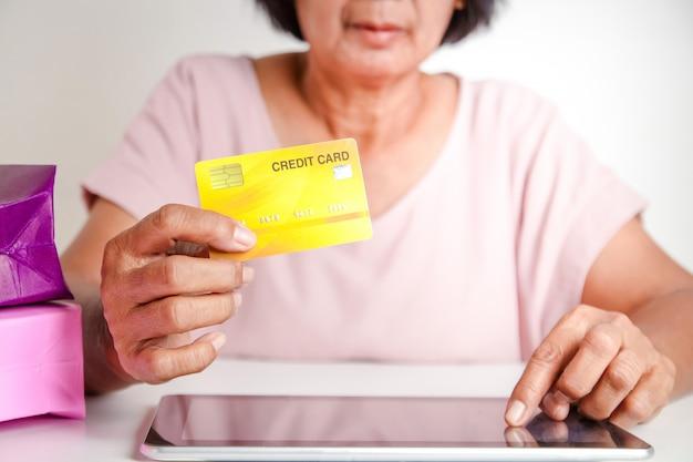 クレジットカードのモックアップを保持しているアジアの年配の女性、タブレット画面を手で押す製品をオンラインで購入する。シニアコミュニティの概念