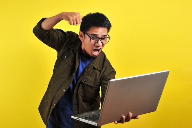 Asian online freelancer very angry in front of his laptop, get bad report from customer, isolated on yellow