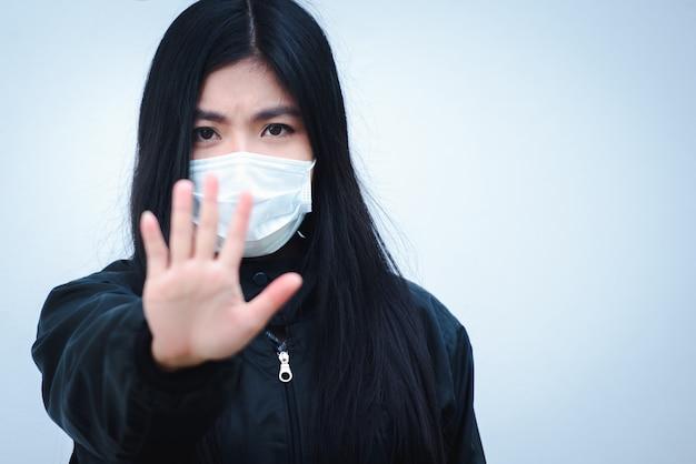 Азиатские или китайские женщины не хотят иметь грипп, вирус толстой кишки, и он болен и носит маску. колона вирус