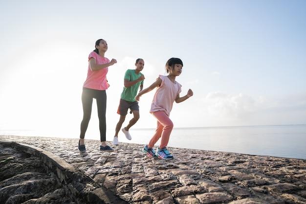 アウトドアスポーツを実行しているアジアの親と子