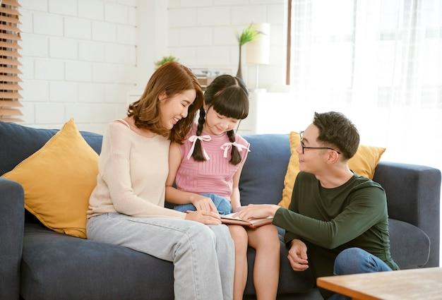 집에서 시간을 보내는 동안 아시아 부모와 딸이 소파에서 책을 읽고