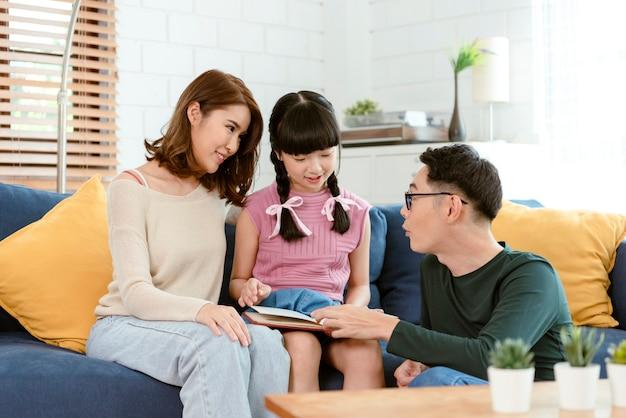 아시아 부모와 딸은 집에서 시간을 보내는 동안 소파에서 책을 읽고 있습니다.
