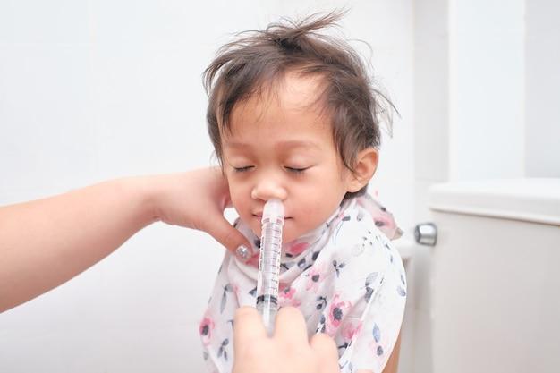 아시아 부모 비강 관개를위한 주사기와 그녀의 아픈 행복 미소 귀여운 2 세 유아 아기 여자 아이 코를 플러시 프리미엄 사진