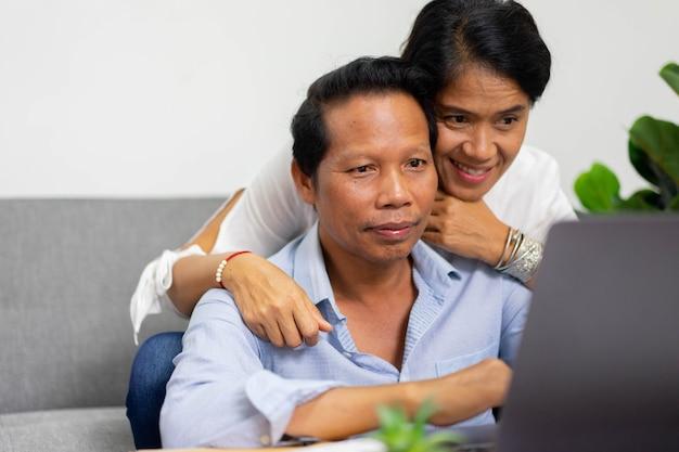 ビデオ通話会議にデジタルタブレットを使用しながらリビングルームに座っているアジアの親
