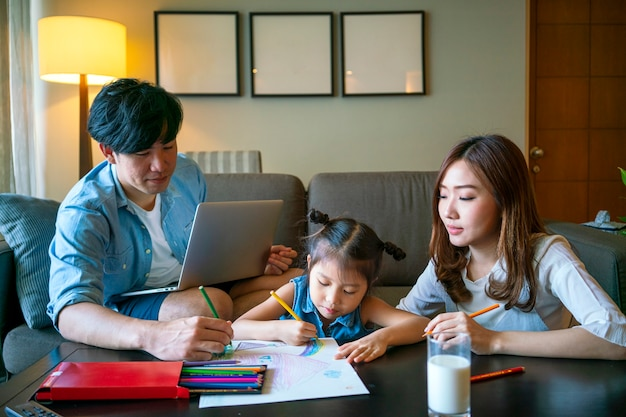Asian parent teaching their daughter doing homework at home