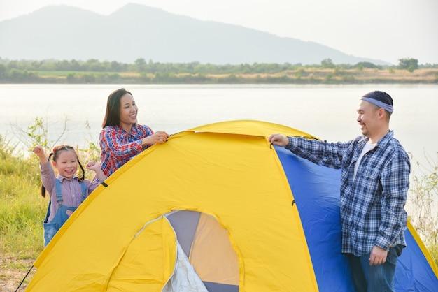 Азиатские родители с дочерью устанавливают палатку на берегу озера. семейное приключение на свежем воздухе в отпуске.