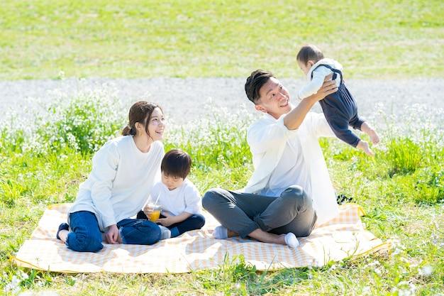 緑豊かなエリアでピクニックを楽しんでいるアジアの親子