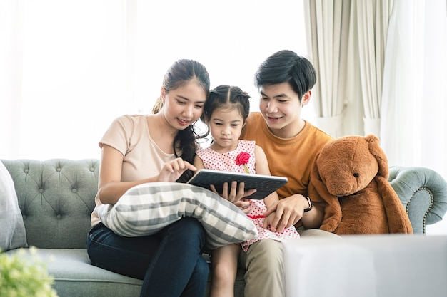 Asian parents and a kid child look at a laptop at home. family concept.