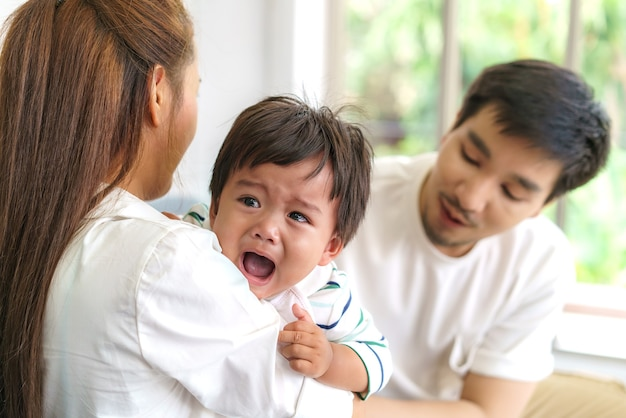 Asian parents with mother and father trying to calm down crying infant son in living room at home