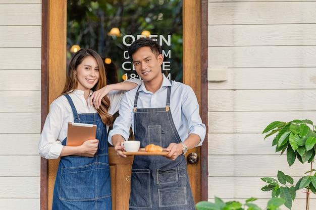 Азиатский партнер владелец малого бизнеса в руках держит чашку кофе с булочной с круассаном