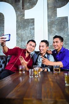 派手なナイトクラブで携帯電話や携帯電話で写真や自分撮りを撮る若い友人のアジアのパーティーの人々のグループ