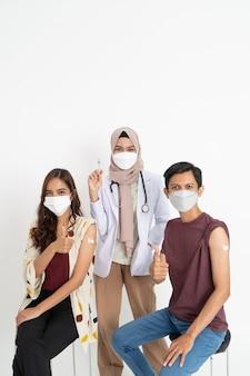 医師によってコロナウイルスの予防接種を受けているアジアの患者