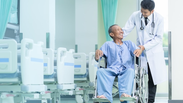 Asian patient in wheelchair sitting in hospital corridor with asian male doctor.