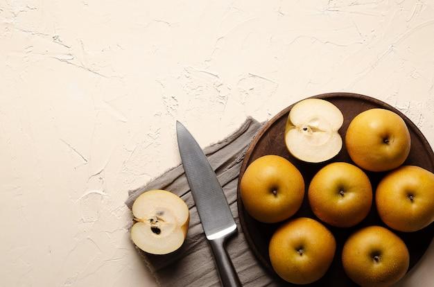 은색 칼로 나무 접시에 아시아 배