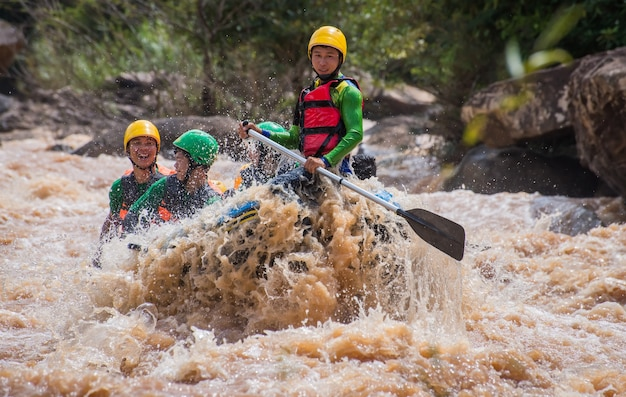 Asian people in action at rafting adventure