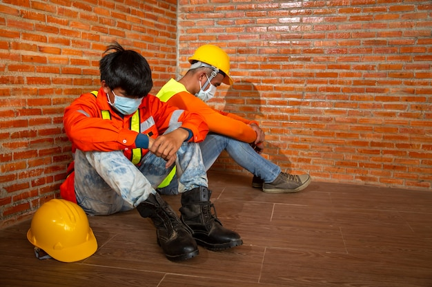 Asian people construction work shutdown due to outbreak of coronavirus disease 2019 or covid-19. concept of economic crisis, worker construction unemployment.