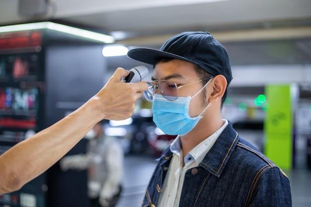 アジアの人々はインフルエンザの温度を測定し、コロナウイルスをチェックします。彼は顔に防護マスクを着ています