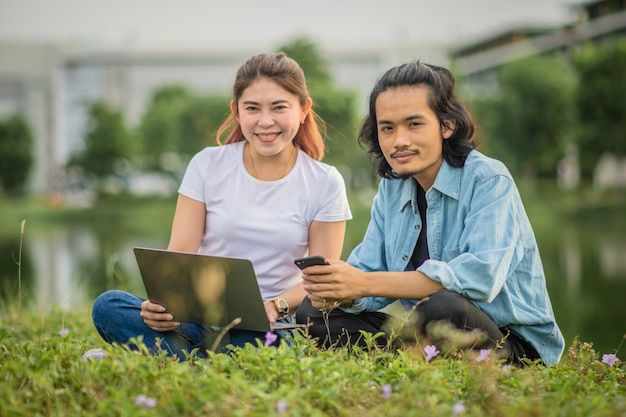 Asian people sitting outdoor using computer city park