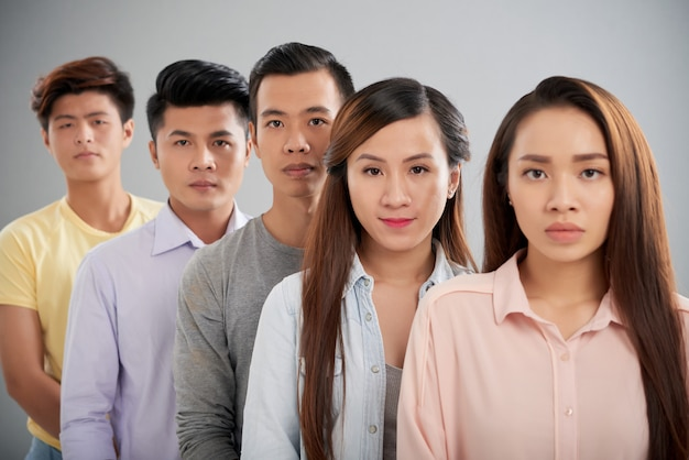 Asian people standing in a rowlooking at camera