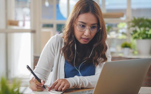 アジアの人々はラップトップコンピューターからインターネット経由でオンラインコースを勉強します