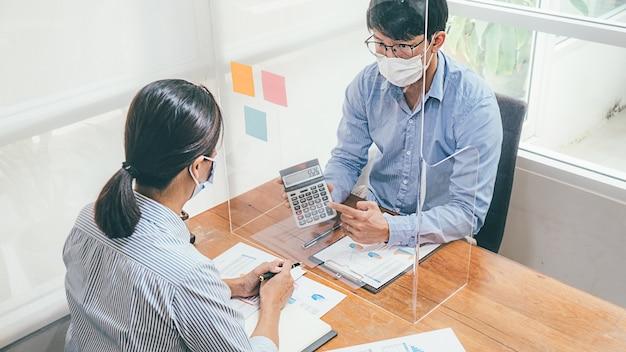 アジアの人々は、医療用マスクを着用して働くチームワークビジネスを成功させました。コロナウイルスの発生状況における民間オフィスの社会的距離からの取り組み