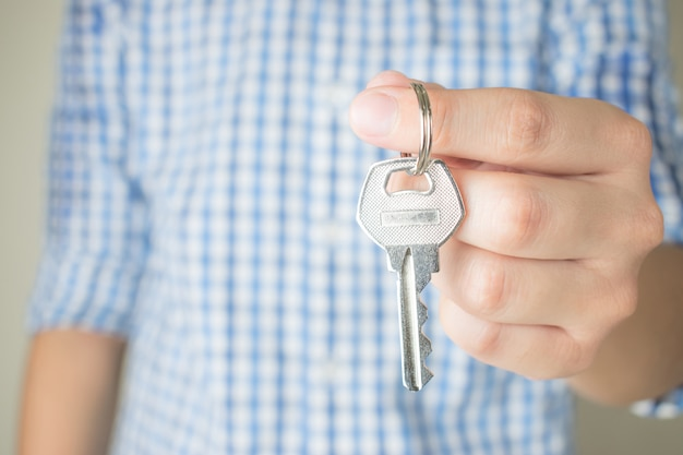 Asian people wear blue plaid shirts holding keys, close up.