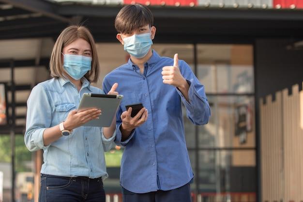 아시아 사람들은 안면 마스크를 쓰고 태블릿 스마트 폰 워킹 스트리트 어반 그런 다음 코로나 바이러스 보호를 위해 마스크 사용